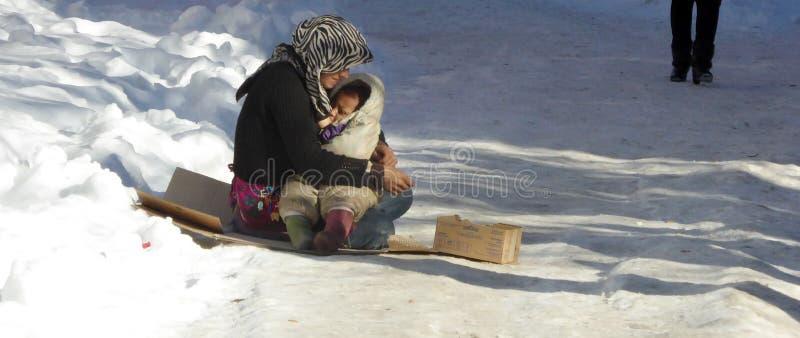 Попрошайка молодой женщины на улице кормит ее младенца грудью стоковые фотографии rf
