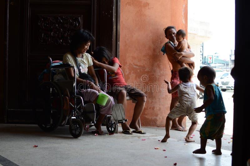 Попрошайка на кресло-коляске при другие попрошайки и дети имея потеху на портале строба двери церков стоковые фото