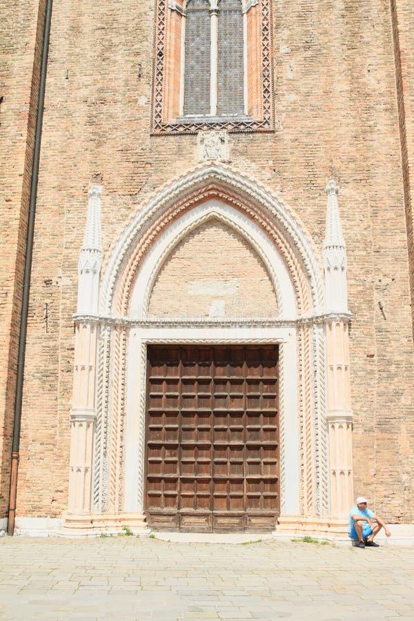 Попрошайка перед церковью в Венеции стоковая фотография