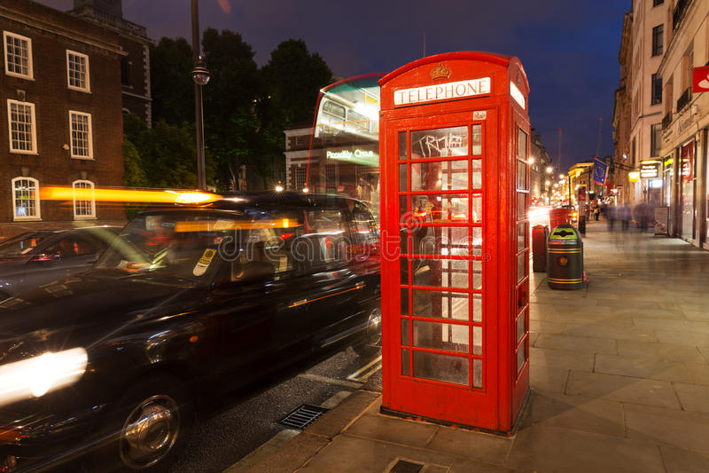 Популярная туристская красная телефонная будка в ноче освещает освещение внутри стоковое фото
