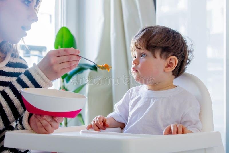 Попытка матери к кормить мальчика малыша с ложкой в стуле стоковые изображения