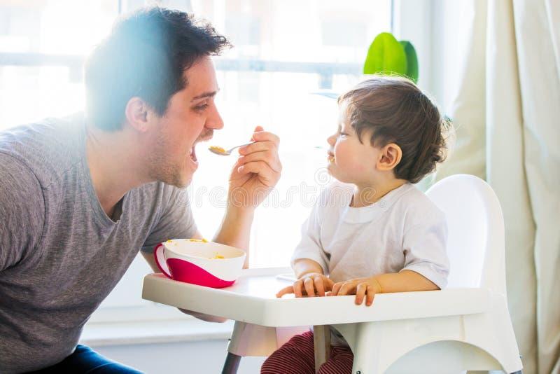 Попытка отца к кормить мальчика малыша с ложкой в стуле стоковая фотография rf