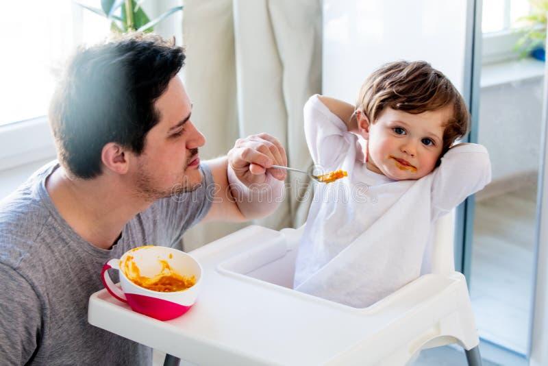 Попытка отца к кормить мальчика малыша с ложкой в стуле стоковое фото