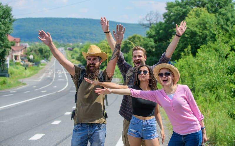 Попытка путешественников для того чтобы остановить автомобиль Автостопщики друзей путешествуя день лета солнечный Путешественники стоковые изображения rf