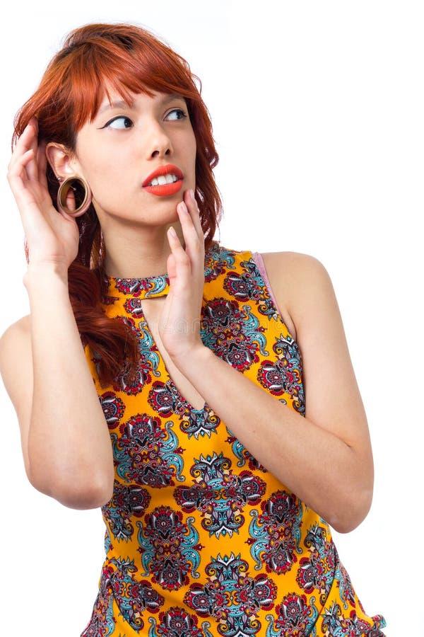 Попытки девушки, который нужно слушать к что-то тщательно Молодая женщина redhead стоковые изображения
