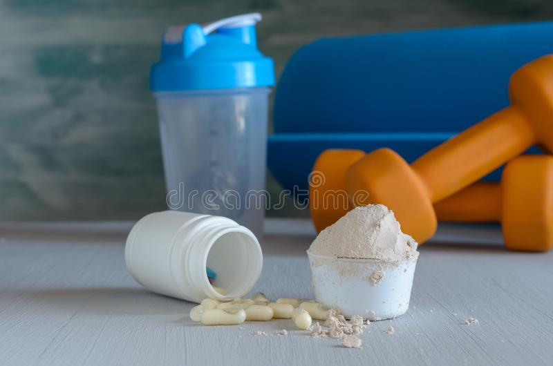 Порошок протеина в ветроуловителе, гантели, циновке йоги и шейкере E стоковые фото