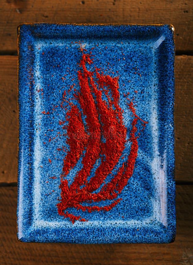 Порошок специи шафрана на голубой плите стоковая фотография rf