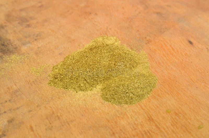 Порошок яркого блеска золота на деревянной предпосылке стоковые изображения