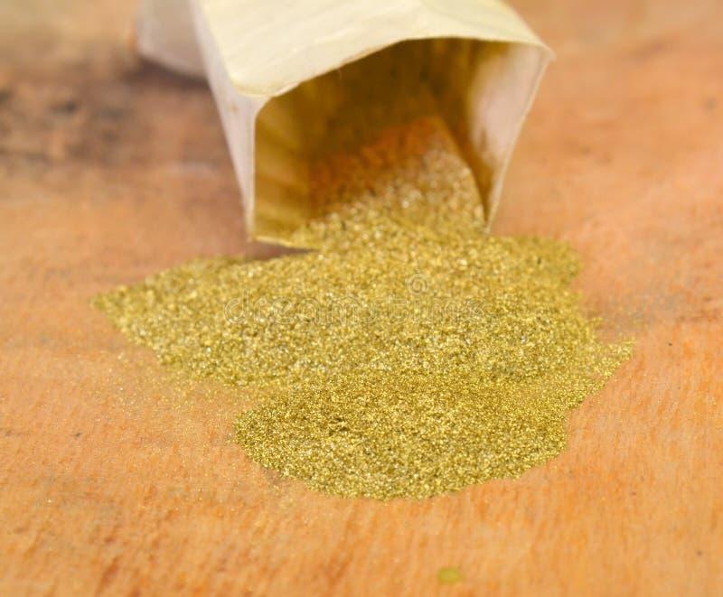 Порошок яркого блеска золота на деревянной предпосылке стоковая фотография
