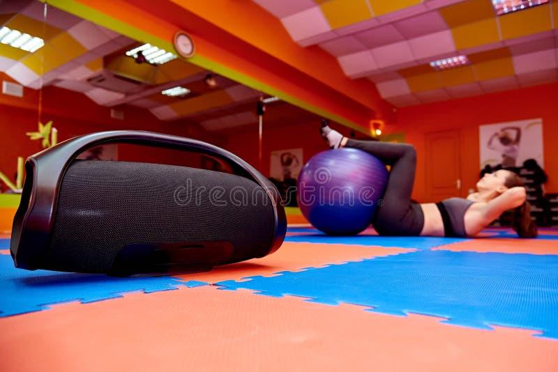 Портативная акустика в комнате аэробики на предпосылке запачканного спорта девушки практикуя стоковые изображения