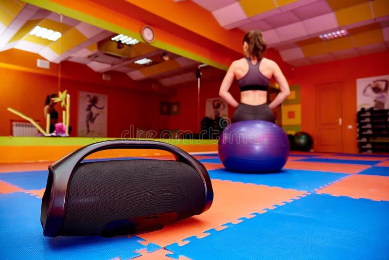 Портативная акустика в комнате аэробики на предпосылке запачканного спорта девушки практикуя стоковое фото rf