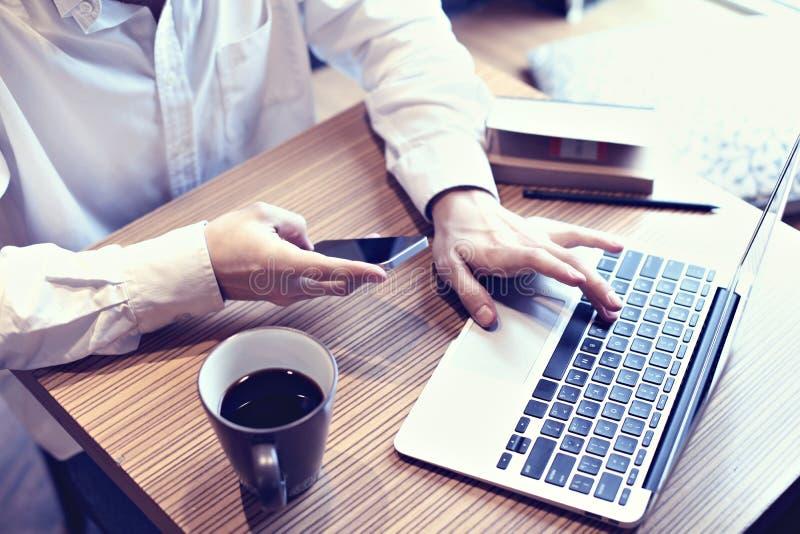 Портативный компьютер и мобильный телефон пользы бизнесмена бухгалтерии в кафе, бизнес-плане сочинительства, выпивая кофе кофе стоковые изображения