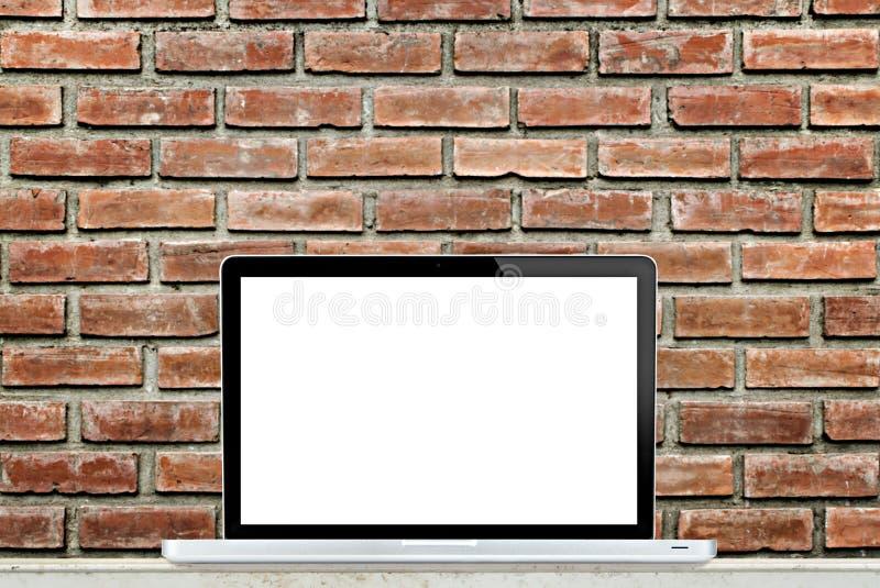 Портативный компьютер на таблице с предпосылкой кирпичной стены стоковые изображения rf