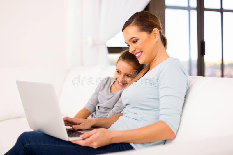 Портативный компьютер дочери матери стоковое фото