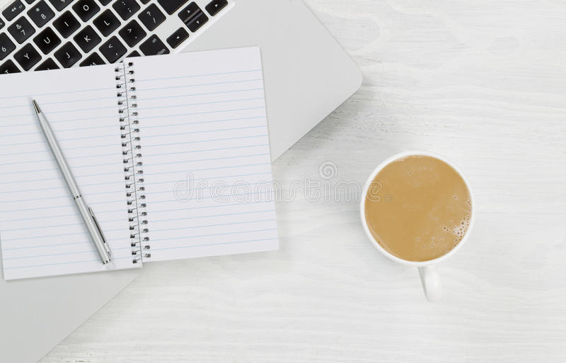 Портативный компьютер с кофе и пустым блокнотом на белом настольном компьютере стоковое изображение rf