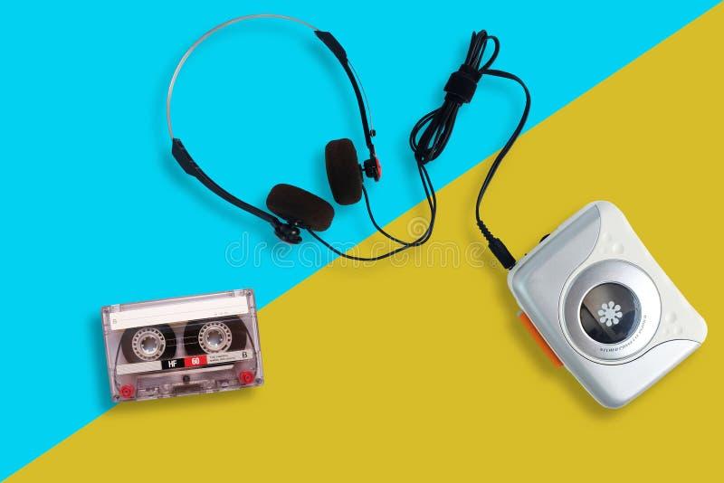 Портативный магнитофон с радио и кассета и наушники на разделенной желтой и голубой предпосылке стоковые фотографии rf
