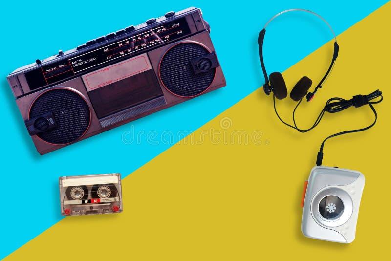Портативный магнитофон с радио и кассета и наушники на разделенной желтой и голубой предпосылке стоковое изображение rf