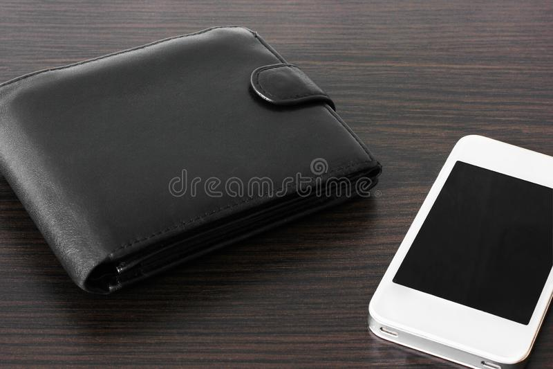 Портмоне и телефон на деревянной предпосылке стоковое фото rf