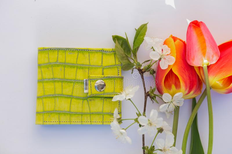 Портмоне лимона на белой предпосылке с тюльпанами стильными стоковые фото