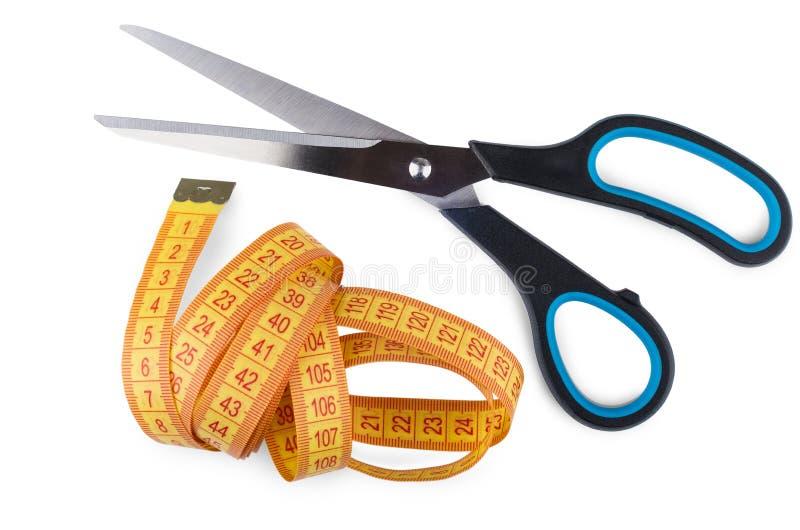 Портновские ножницы и лент-линия изолированные на белизне стоковые фото