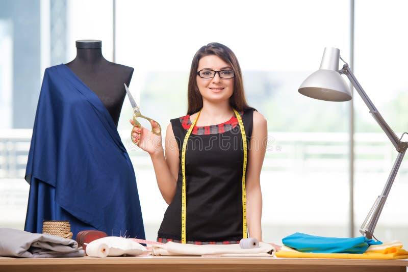 Портной женщины работая на новой одежде стоковые изображения rf