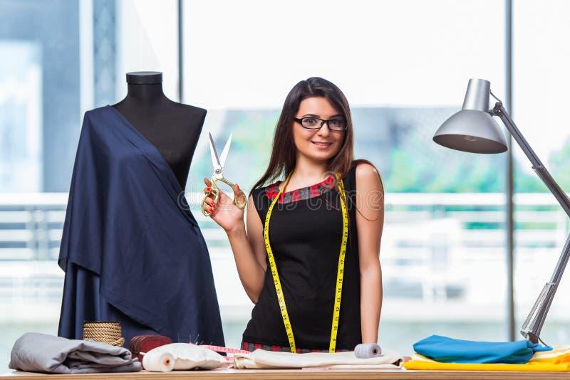 Портной женщины работая на новой одежде стоковое изображение
