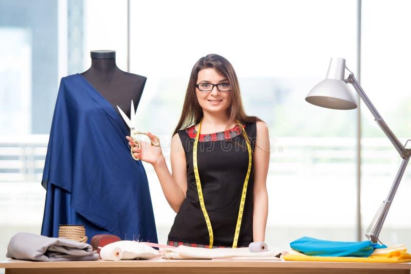 Портной женщины работая на новой одежде стоковая фотография