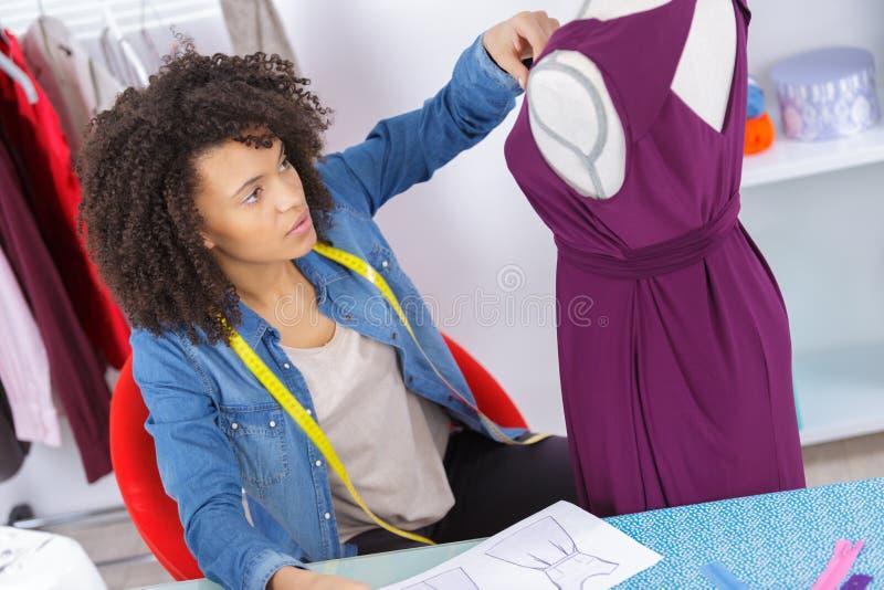 Портной женщины работая на новом платье стоковое фото rf