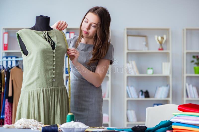 Портной женщины работая на одежде шить шить измеряя fa стоковое фото