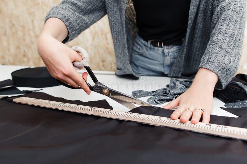 Портняжничайте резать вне темную ткань с большими ножницами стоковые изображения