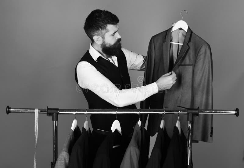 Портняжничайте с занятой стороной около изготовленных на заказ курток на красной предпосылке Современная концепция выбора шкафа Д стоковое фото rf