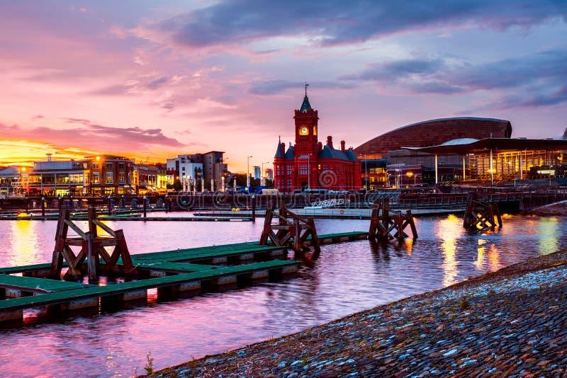 Портовый район на ноче в Кардиффе, Великобритании Небо захода солнца красочное с центром тысячелетия Уэльс стоковая фотография