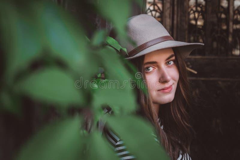 Портретная красивая женщина в полосатой рубашке, держащая шляпу и гляд стоковые изображения rf