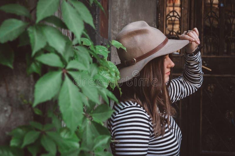 Портретная красивая женщина в полосатой рубашке, держащая шляпу на зад стоковая фотография rf
