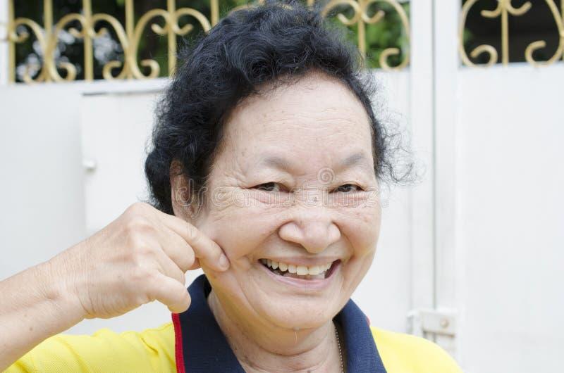 Портрет азиатский старший усмехаться женщины стоковое фото
