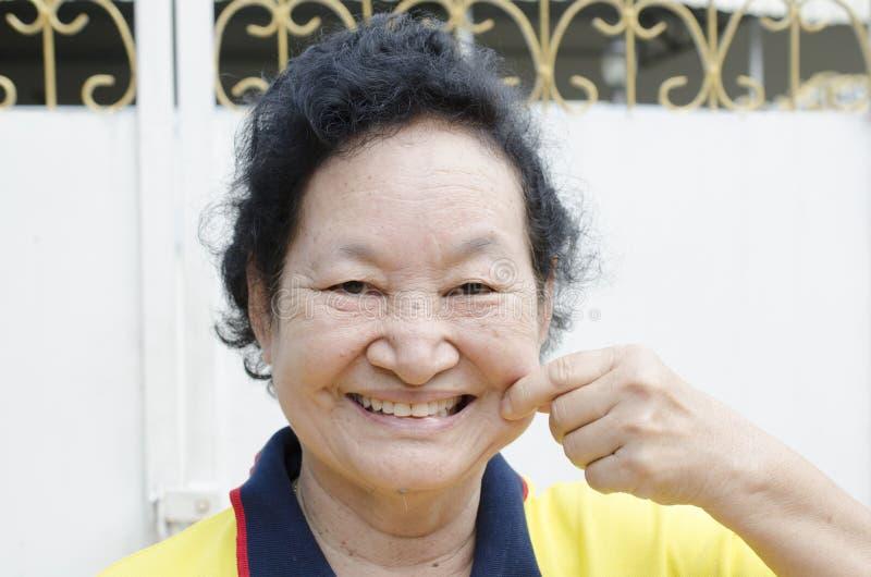 Портрет азиатский старший усмехаться женщины стоковые изображения