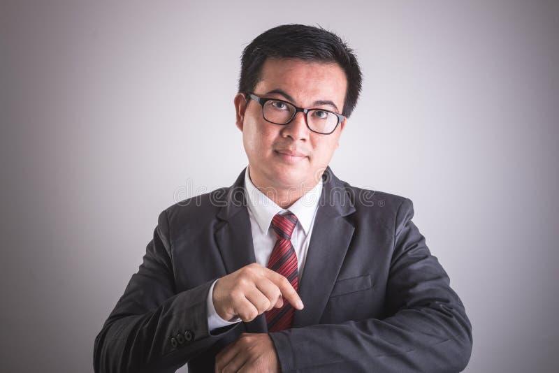Портрет азиатского бизнесмена с пунктом руки на его времени запястья руки стоковая фотография