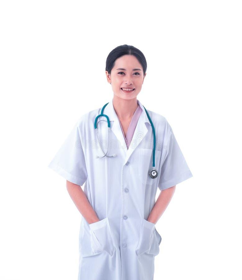 Портрет азиатского доктора молодой женщины в форме и стетоскопе на шеи думающ и смотрящ камеру с усмехаться изолированный на w стоковое фото rf
