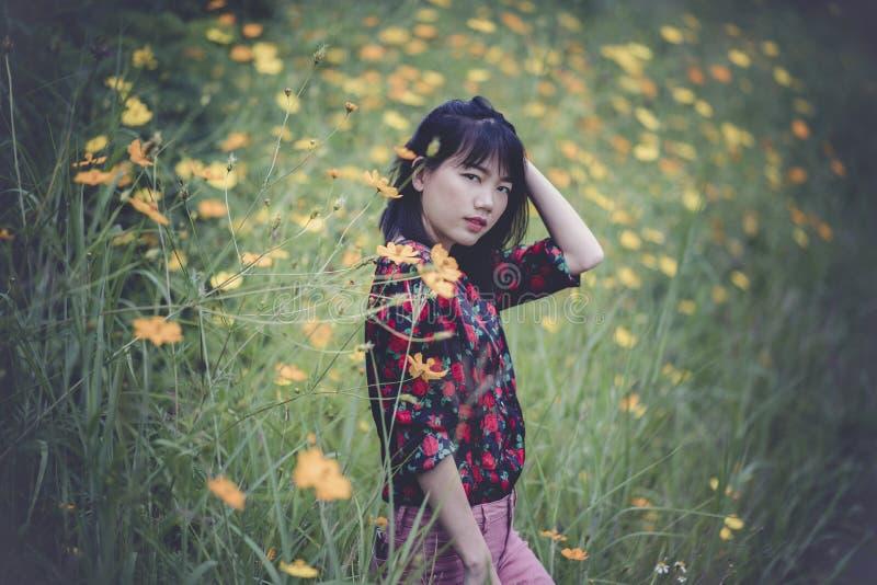Портрет азиатского представления модели более молодой женщины в желтое bloo цветка стоковое фото