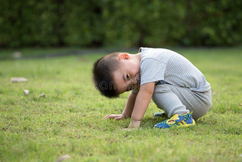 Портрет азиатского ребенка сидя в парке стоковая фотография