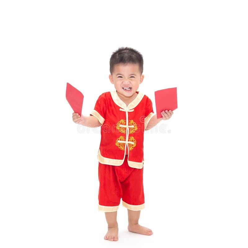 Портрет азиатского ребенка стоя и держа красный пакет стоковое изображение rf