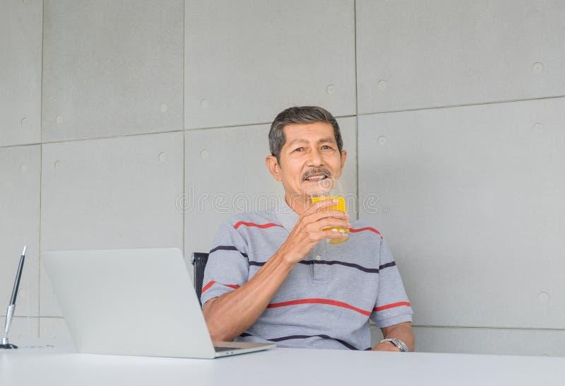 Портрет азиатского старшего человека имел белую бороду усаживание случайных одежд платья и поднять стеклянный апельсиновый сок дл стоковое фото