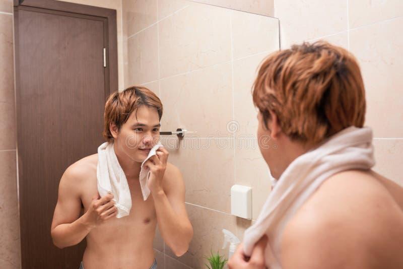 Портрет азиатского человека моя в ванной комнате стоковое фото