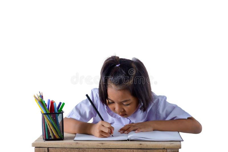 Портрет азиатской девушки в школьной форме рисует с карандашами цвета изолированными на белой предпосылке стоковая фотография