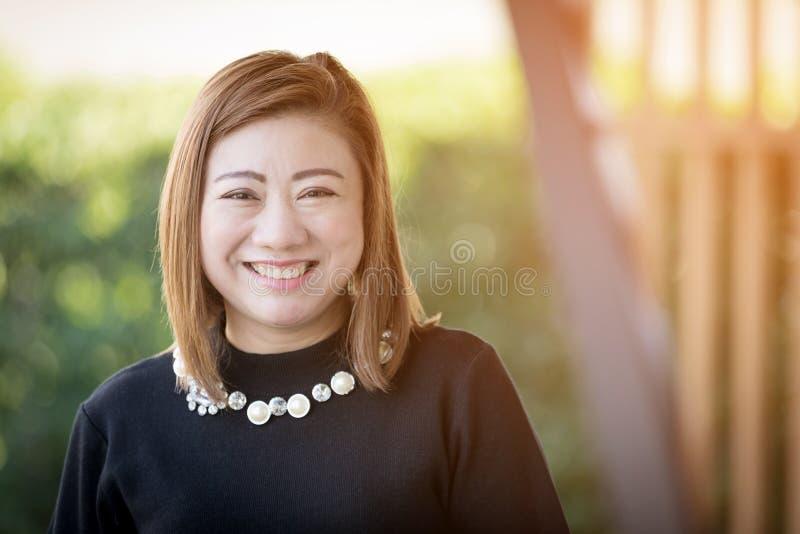 Портрет азиатской женщины женщины smAsian усмехаясь счастливый с солнечным светом i стоковые изображения rf