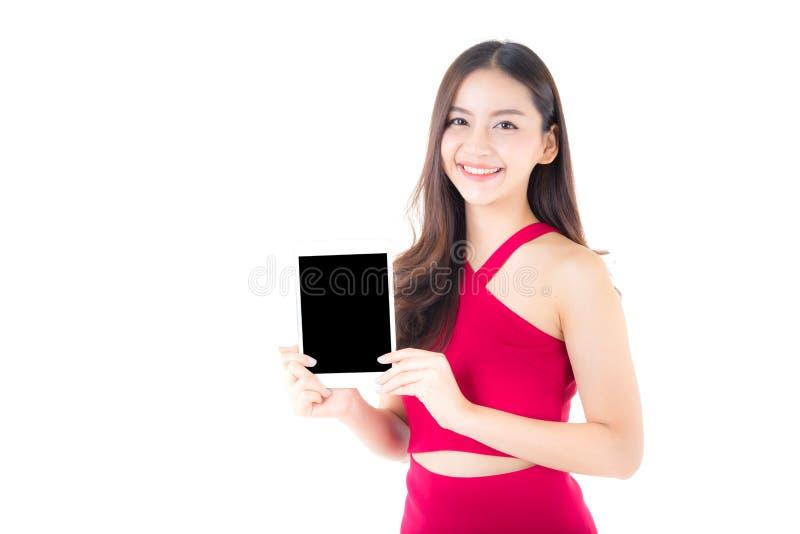 Портрет азиатской молодой женщины при красное платье стоя показывающ таблетку пустого экрана стоковое изображение