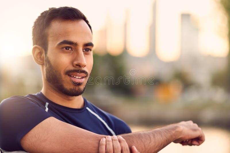 Портрет активного millenial человека jogging на сумраке с городскими городским пейзажем и заходом солнца на заднем плане стоковые фотографии rf