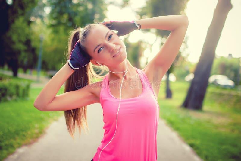 Портрет атлетической девушки разрабатывая и протягивая в парке стоковое фото rf