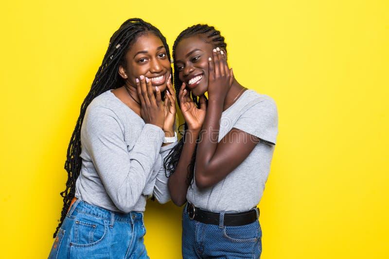 Портрет 2 африканских молодых женщин обнимая и смеясь над желтой предпосылкой стоковое изображение rf