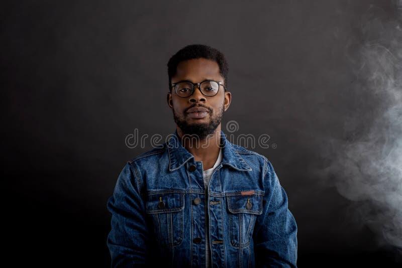 Портрет африканского парня в куртке джинсовой ткани в темноте стоковые фотографии rf
